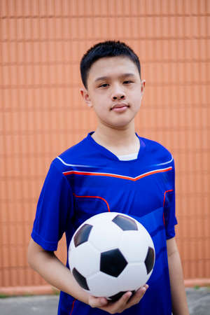Photo for Football boy hold the ball in front of brown wall. - Royalty Free Image