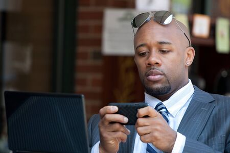 Photo pour A good looking African American business man works on his laptop or netbook computer with a smart phone in his hands. - image libre de droit