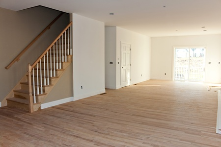 Photo pour New home construction interior room with unfinished wood floors stairway and railings. Electrical and hvac connections also are partially unfinished. - image libre de droit