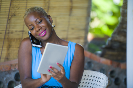 portrait of young beautiful happy and busy black afro American woman working at coffee shop talking on mobile phone while networking on digital tablet pad in internet freelancer job success concept