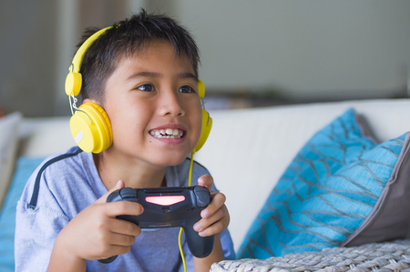 lifestyle portrait of young Latin little child excited and happy playing video game online with headphones holding controller having fun sitting on couch in gamer emotion and kid gaming addiction