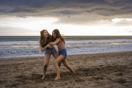 Photo pour two happy and attractive young Asian Chinese women girlfriends or sisters having fun playing wrestling on sunset beach in beautiful light enjoying summer holidays travel together carefree - image libre de droit