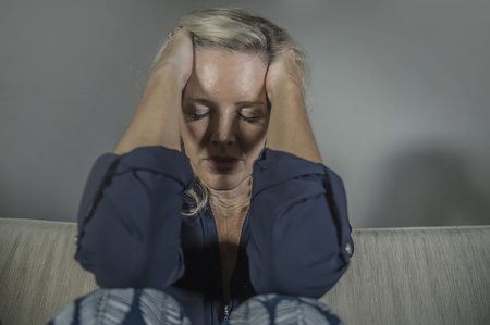 lifestyle portrait of attractive and sad woman with headache and migraine feeling frustrated and anxious sitting at home sofa couch depressed suffering anxiety crisis and depression problem