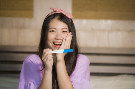 young happy and excited pregnant Asian Chinese woman at home holding predictor and checking positive result on pregnancy test feeling blessed expecting baby in fertility concept