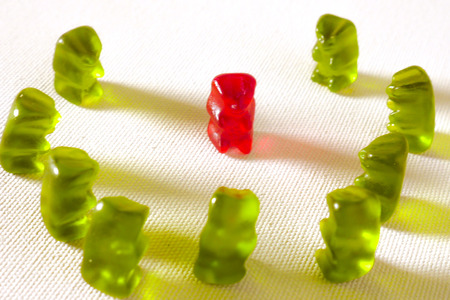 Photo pour sweet candy gummy teddy bears representing group of students or work colleagues bullying and mobbing helpless victim in harassment and abuse social problem concept isolated on white background - image libre de droit