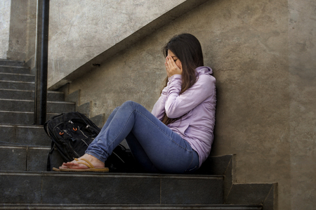 Foto de young sad and depressed student woman or bullied teenager girl sitting outdoors on street staircase scared and anxious victim of bullying feeling desperate suffering depression problem - Imagen libre de derechos