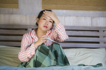 young beautiful and sweet Asian Korean girl in pajamas feeling sick at home bedroom suffering cold and flu taking temperature with thermometer in bed covered with blanket with virus infection