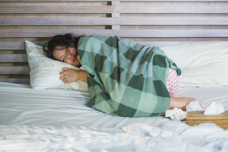 young sick sweet Asian Korean girl in pajamas covered with blanket lying feverish on bed suffering cold and flu in medical health care and influenza virus disease concept
