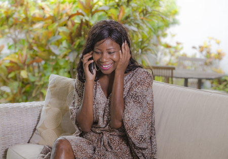 young beautiful and happy black afro American woman talking on mobile phone cheerful and relaxed sitting at sofa couch in hotel resort or luxury villa garden in communication concept