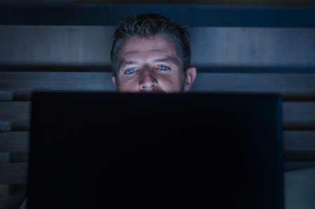 Photo pour young attractive and relaxed internet addict man networking concentrated late at night on bed with laptop computer in social media addiction or workaholic businessman concept - image libre de droit