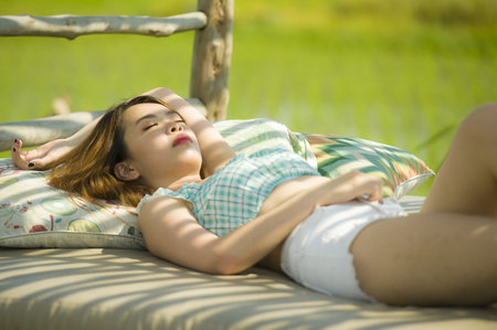 Photo pour young beautiful and sexy Asian Korean woman lying comfortable at holidays resort garden bed having sunbath tanning relaxed and chilled in Summer vacation and beauty concept - image libre de droit