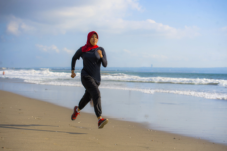 Foto de young healthy and active runner Muslim woman in Islam hijab head scarf running and jogging on the beach wearing traditional arab sport clothes in fitness workout and weight loss concept - Imagen libre de derechos