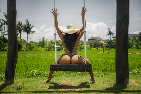 Foto de young attractive and relaxed woman with sexy body having fun on swing enjoying holidays trip at tropical paradise island wearing bikini and Summer hat in tourism and vacation concept - Imagen libre de derechos
