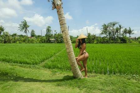 Foto de young sexy and happy Southeast Asian woman in tradition rural hat posing in bikini at beautiful rice field landscape in Asia tourism and Summer holidays travel concept - Imagen libre de derechos