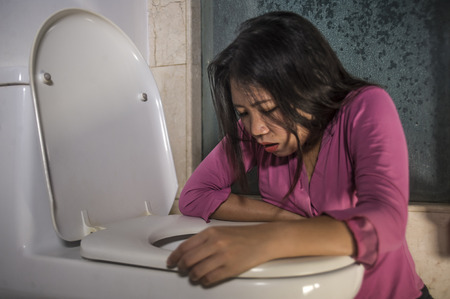 Foto de young drunk or pregnant Asian woman vomiting and throwing up in toilet WC feeling unwell and sick suffering stomach ache and nausea as pregnancy symptom or intoxicated in hangover - Imagen libre de derechos