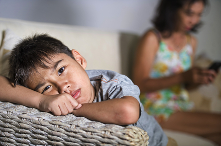 young sad and bored 7 or 8 years old Asian child at home couch feeling frustrated and unattended while mother networking on mobile phone as internet addict neglecting her son