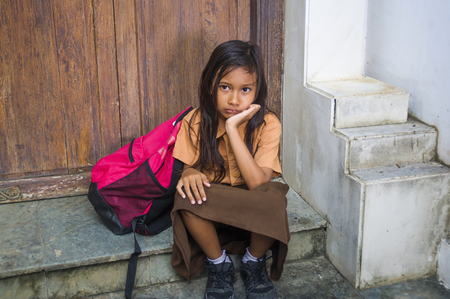Foto de 7 or 8 years child in school uniform sitting outdoors sad and depressed with her backpack on the stairs suffering bullying and abuse problem feeling alone and helpless in scared schoolgirl concept - Imagen libre de derechos