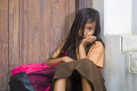 Photo pour 7 or 8 years child in school uniform sitting outdoors sad and depressed with her backpack on the stairs suffering bullying and abuse problem feeling alone and helpless in scared schoolgirl concept - image libre de droit