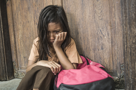 Foto de 7 or 8 years child in school uniform sitting outdoors on the floor crying sad and depressed holding her backpack suffering bullying and abuse problem feeling alone and helpless as scared schoolgirl - Imagen libre de derechos