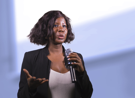 Foto de young attractive and confident black African American business woman with microphone speaking in auditorium at corporate event or seminar giving motivation and success coaching conference - Imagen libre de derechos