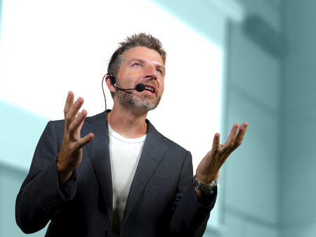 Foto de young attractive and confident successful man with headset speaking at corporate business coaching and training auditorium conference room talking giving motivation training from speaker stage - Imagen libre de derechos