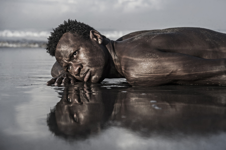 Foto für artistic expressive portrait of young attractive and sexy black African American man with athletic muscular body posing cool in sea water on desert beach in male beauty and holidays concept - Lizenzfreies Bild