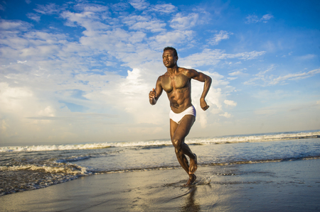 Photo pour young happy and attractive black afro American man with fit healthy and muscular body running on beach sea water having fun enjoying Summer holidays feeling free and cheerful - image libre de droit