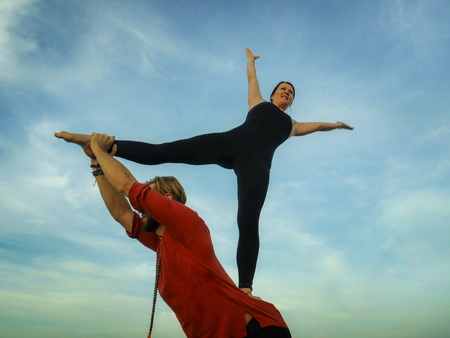 Photo pour young attractive and beautiful acrobat couple practicing acroyoga exercise concentrated keeping balance practiing yoga on the beach in relaxation and meditation concept and healthy lifestyle - image libre de droit