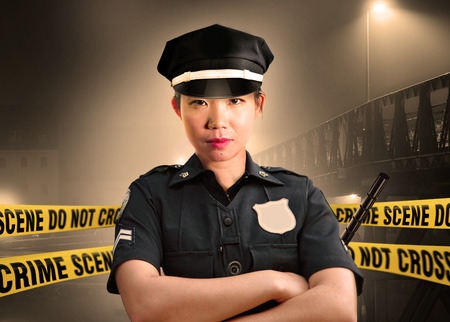 Photo for young Asian American police officer standing serious in custody of crime scene for preserving evidence at do not cross police line yellow tape in murder investigation and law enforcement concept - Royalty Free Image