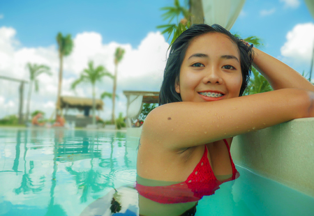 Photo pour outdoors portrait of young beautiful and sweet Asian Indonesian teenager girl swimming at tropical resort pool smiling happy and cheerful enjoying relaxed holidays trip having fun in tourism concept - image libre de droit