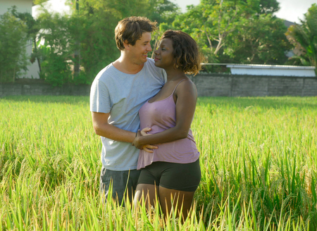 Photo for young happy and beautiful mixed ethnicity couple with black afro American woman and attractive Caucasian man cuddling and having fun enjoying holidays at rice field in multiracial love - Royalty Free Image