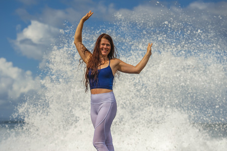 Photo for young happy and attractive red hair woman playing excited spreading arms feeling free and relaxed getting wet by sea waves splashing on her enjoying beach holidays trip and healthy lifestyle - Royalty Free Image