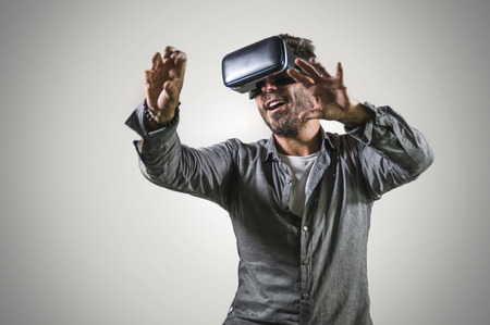 Photo pour young happy and excited man wearing virtual reality VR goggles headset experimenting 3d illusion playing video game touching illusion environment surprised isolated on studio background - image libre de droit