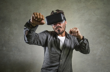 Photo pour young happy and excited man wearing virtual reality VR goggles headset experimenting 3d illusion playing fight or boxing video game enjoying punching isolated on grunge background - image libre de droit