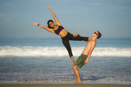 Photo pour outdoors lifestyle portrait young attractive and concentrated couple of yoga acrobats practicing acroyoga balance and meditation exercise on beautiful beach in mind and body teamwork control - image libre de droit