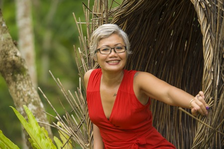 Foto de natural lifestyle portrait of attractive and happy middle aged 40s or 50s Asian tourist woman with grey hair and elegant red dress sitting outdoors at tropical jungle relaxed admiring beauty of nature - Imagen libre de derechos