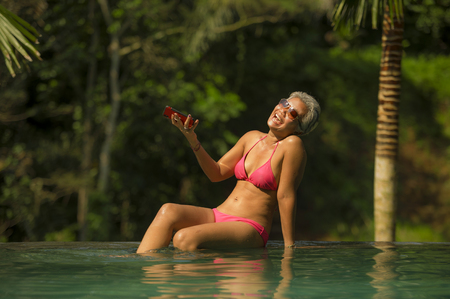 Foto de attractive and happy middle aged Asian Indonesian woman in bikini swimming at tropical luxury resort infinity pool taking selfie portrait with mobile phone enjoying Summer holiday destination - Imagen libre de derechos