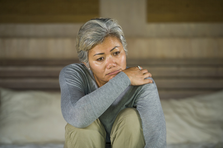 Photo pour desperate 40s - 50s mature lady, dramatic lifestyle home portrait of attractive sad and depressed middle aged woman with grey hair on bed feeling upset suffering depression and anxiety - image libre de droit