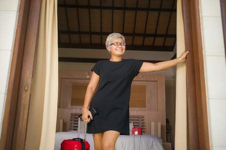 lifestyle portrait of natural attractive and happy middle aged Asian woman in stylish Summer dress arriving to hotel opening room balcony door looking delighted enjoying travel holidays getaway