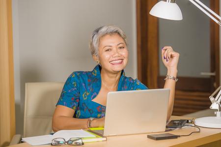 Foto de woman business success. Lifestyle portrait of Happy and attractive elegant middle aged Asian businesswoman working smiling at office computer desk feeling positive and successful - Imagen libre de derechos