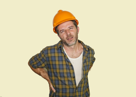 Photo for upset and exhausted construction worker or repair man wearing builder helmet complaining suffering pain in his lower back after working hard isolated on even background - Royalty Free Image