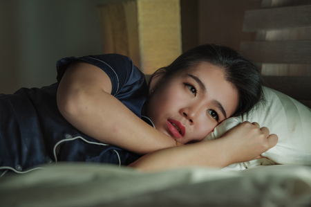 Photo pour home lifestyle portrait of young beautiful sad and depressed Asian Chinese woman awake in bed late night suffering anxiety crisis and depression problem feeling desperate after relationship break up - image libre de droit