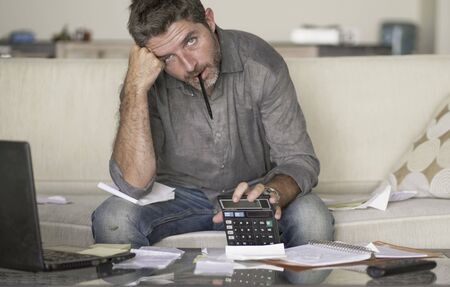 Foto für young stressed and desperate man at home living room couch doing domestic accounting with paperwork and calculator feeling overwhelmed and worried suffering financial crisis debt and ruin - Lizenzfreies Bild