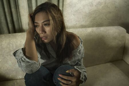 young beautiful sad and depressed Asian woman in pain thoughtful and confused at home couch feeling broken heart suffering depression crisis and anxiety problem