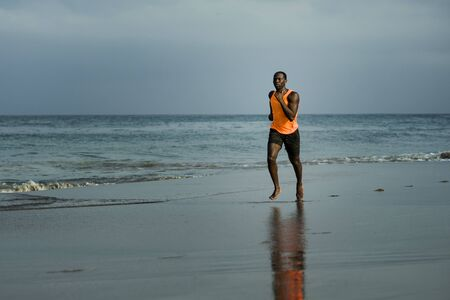 Photo pour athletic full body portrait of young attractive and fit black African American man running on the beach doing Summer fitness jogging workout at the sea in sport exercise and healthy lifestyle concept - image libre de droit