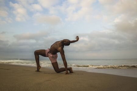Photo for contemporary dance choreographer and dancer doing ballet beach workout . a young attractive and athletic black African American man dancing on sunrise doing dramatic performance - Royalty Free Image