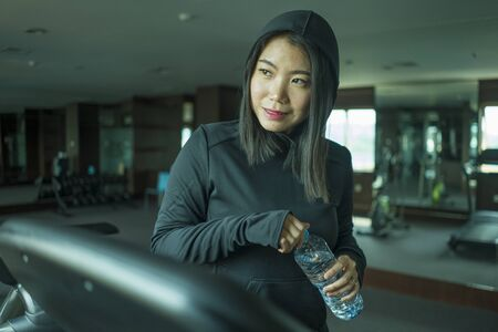 young happy and attractive Asian Korean woman drinking water during fitness center workout smiling cheerful training at hotel gym in body care and healthy lifestyle concept