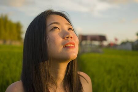 Photo for young happy and beautiful Asian woman enjoying nature at rice field. sweet Chinese girl in Summer dress at green field exploring countryside during holiday travel in wanderlust and tourism - Royalty Free Image