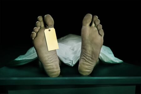 Photo for Male human body lying dead at morgue with blank identity label and covered with sheet . Close-up foot of man cadaver with identification toe tag in human life loss and death concept isolated on black - Royalty Free Image