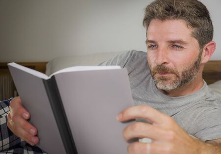 Photo pour lifestyle portrait of young attractive and relaxed man at home lying comfortable on bed wearing  pajamas reading a book enjoying an interesting novel chilled and cozy - image libre de droit